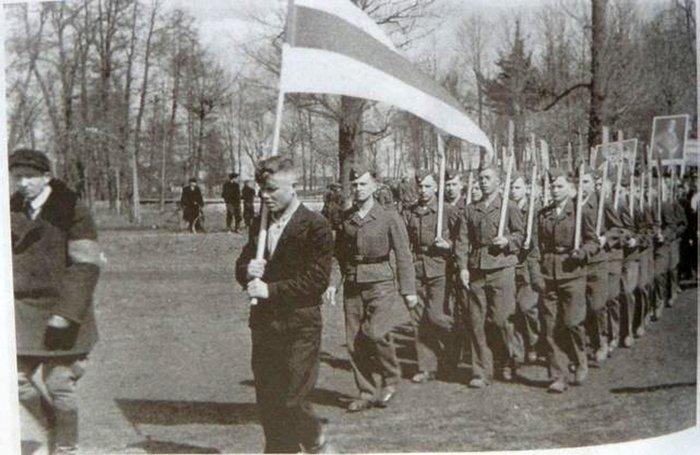 На фото коллаборационисты, марширующие под бело–красно–белым флагом.